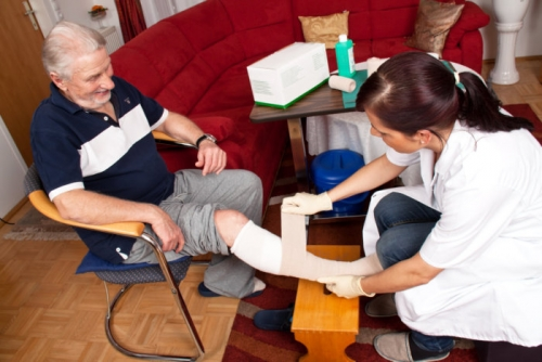 caregiver taking care of an elderly man's wound