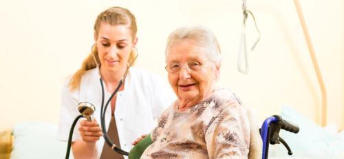 caregiver checking elderly woman's blood pressure