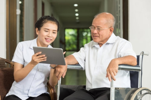 caregiver showing tablet to an elderly man